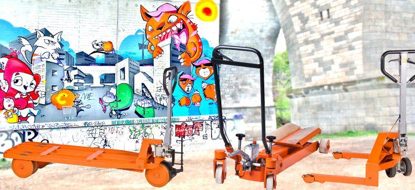 drei verschiedene Sonderhubwagen vor einer Graffitimauer